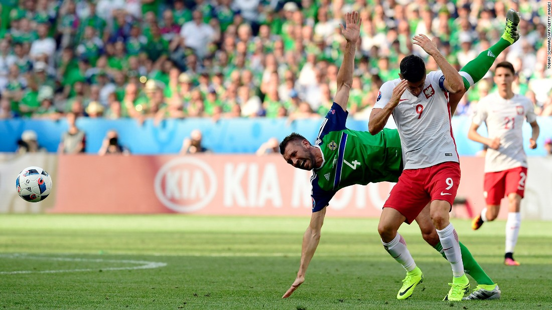 Northern Ireland's Gareth McAuley, left, tangles with Poland's Robert Lewandowski.
