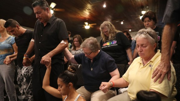 A man injured in the attack stands with other mourners as they attend a memorial service at an Orlando church.