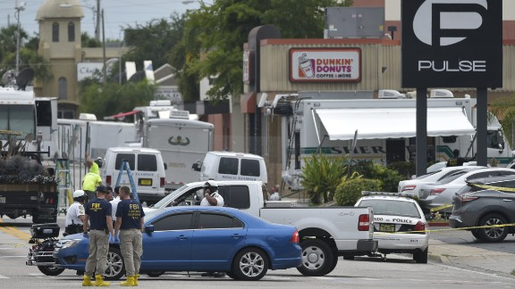 "Police and investigators work near the area of the mass shooting at the Pulse nightclub on in Orlando, Florida on June 12, 2016. A somber President Barack Obama  expressed grief and outrage at the ""horrific massacre"" of 50 late-night revelers at an Orlando gay club, branding it an act of terror and hate. / AFP / Mandel Ngan        (Photo credit should read MANDEL NGAN/AFP/Getty Images)"