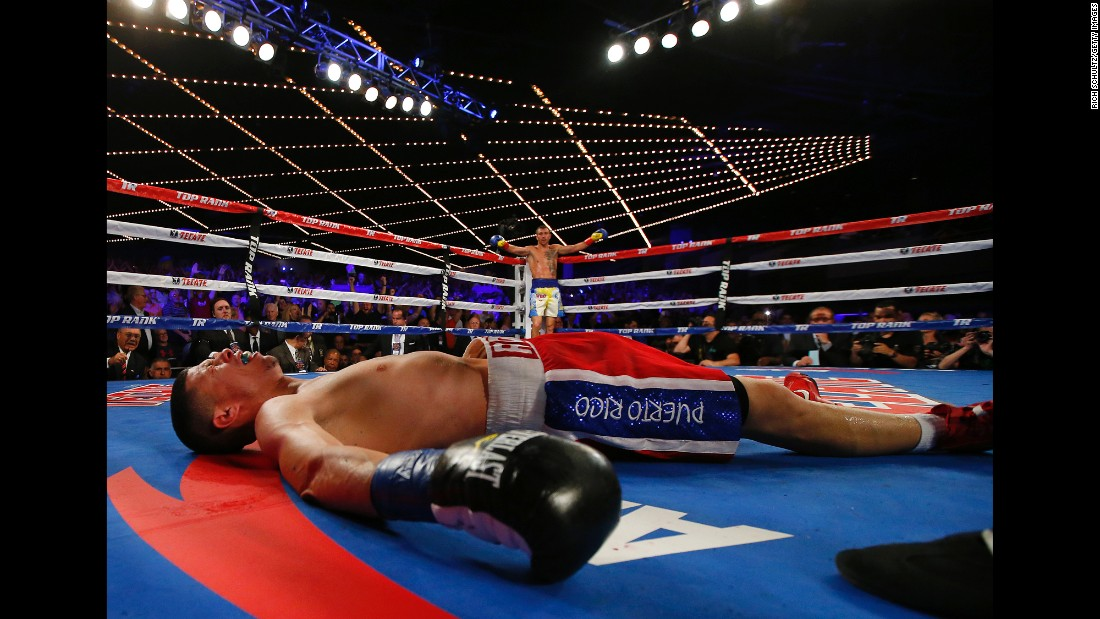 Vasyl Lomachenko raises his arms in victory after knocking out Roman Martinez to win the WBO junior lightweight title on Saturday, June 11.