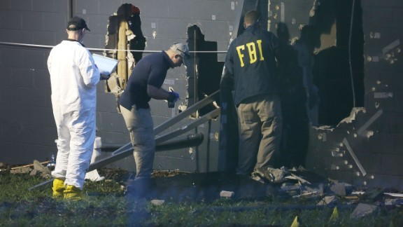 FBI agents investigate near the damaged rear wall of the Pulse Nightclub where Omar Mateen allegedly killed at least 50 people on June 12, 2016 in Orlando, Florida. The mass shooting killed at least 50 people and injuring 53 others in what is the deadliest mass shooting in the country