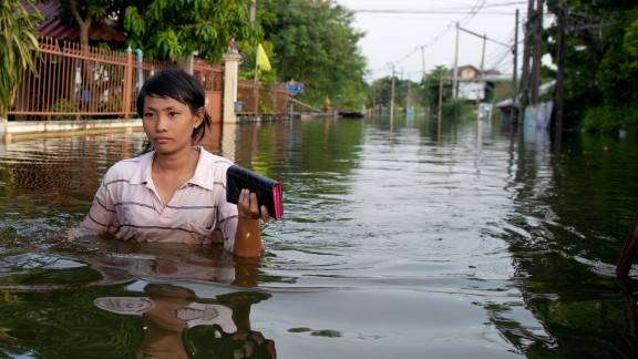 PATHUMTHANI, THAILAND - OCTOBER 21: A Thai woman walks  through the deep flooded streets October 21, 2011 in Pathumthani on the outskirts of Bangkok, Thailand. Hundreds of factories closed in the central Thai province of Ayutthaya and Nonthaburi as the waters come closer to threaten Bangkok as well. Around 320 people have died in flood-related incidents since late July according to the Department of Disaster Prevention and Mitigation. Thailand is experiencing the worst flooding in 50 years with damages running as high as $6 billion which could increase of the floods swamp Bangkok.  (Photo by Paula Bronstein/Getty Images)