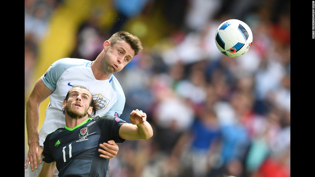 England defender Gary Cahill heads the ball away from Bale.