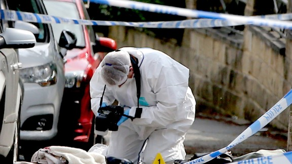 A forensics officer takes photos of items at the scene of the attack.