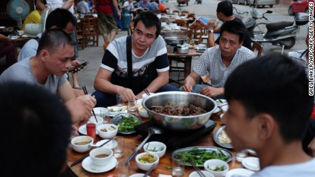 This photo taken on May 9, 2016 shows people eating dog meat at a restaurant in Yulin, in China's southern Guangxi region. International groups and celebrities, backed by millions of foreign petitioners, have rallied against an annual dog meat festival in the Chinese city of Yulin: but the protests may have backfired, residents say, spurring more people to eat man's best friend. / AFP / GREG BAKER / TO GO WITH AFP STORY CHINA-ANIMAL-DOG-FOOD, FOCUS BY BENJAMIN CARLSON        (Photo credit should read GREG BAKER/AFP/Getty Images)