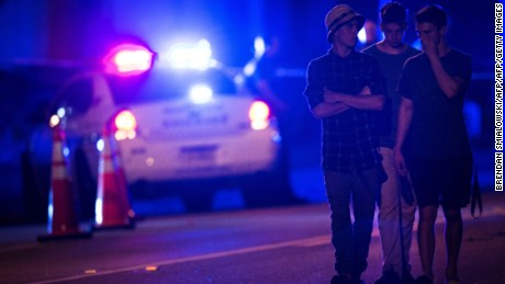 People walk by a police roadblock near the Pulse nightclub on June 12, 2016 in Orlando, Florida.