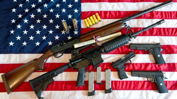 """This February 4, 2013 photo illustration in Manassas, Virginia, shows a Remington 20-gauge semi-automatic shotgun, a Colt AR-15 semi-automatic rifle, a Colt .45 semi-auto handgun, a Walther PK380 semi-auto handgun and various ammunition clips with a copy of the US Constitution on top of the American flag. US President Barack Obama Monday heaped pressure on Congress for action """"soon"""" on curbing gun violence. Obama made a pragmatic case for legislation on the contentious issue, arguing that just because political leaders could not save every life, they should at least try to save some victims of rampant gun crime."""
