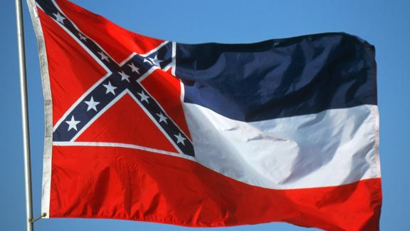 "Adopted by the Mississippi Legislature in 1894. The thirteen stars, sometimes said to represent the number Confederate States and those that might have been Confederate, are said to represent the ""original number of States of the Union"" in the original description"