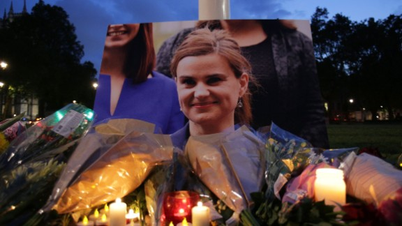 Floral tributes and candles are placed by a picture of slain Labour MP Jo Cox at a vigil in Parliament square in London on June 16, 2016. Cox died today after a shock daylight street attack, throwing campaigning for the referendum on Britain