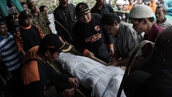 Indonesian villagers prepare for the funeral of a landslide victim in Banjarnegara on Sunday.