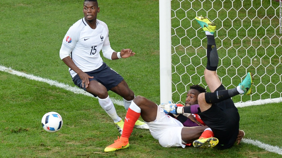 Switzerland's defender Johan Djourou , center, vies on the ground with France's goalkeeper Hugo Lloris, right, beside  midfielder Paul Pogba of France.