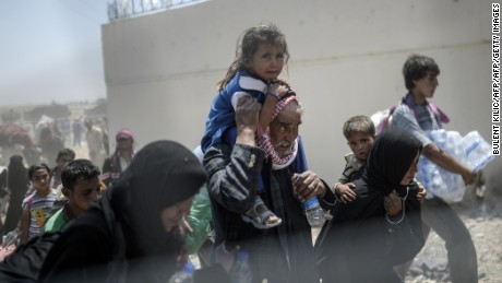 Syrians fleeing the war walk towards the border gates at the Akcakale border crossing, in Sanliurfa province on June 15, 2015. Turkey said it was taking measures to limit the flow of Syrian refugees onto its territory after an influx of thousands more over the last days due to fighting between Kurds and jihadists. Under an 'open-door' policy, Turkey has taken in 1.8 million Syrian refugees since the conflict in Syria erupted in 2011. / AFP / BULENT KILIC (Photo credit should read BULENT KILIC/AFP/Getty Images)