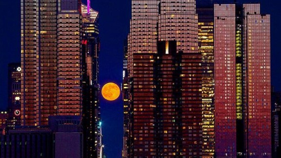 """The summer solstice featured a full """"strawberry"""" moon. The name comes from the belief that strawberry-picking season is at its peak during this time, according to the Farmer's Almanac. The moon hovered above 42nd Street in New York City as the skyline glowed from the setting sun on Monday."""