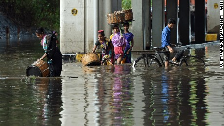 Indians wade through a flooded street Tuesday in Mumbai.