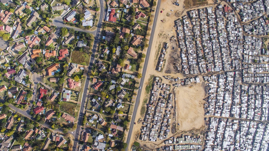 Miller started photographing above Cape Town, though is project has spread to Durban, Johannesburg and Alexandra. In his aerial shots, the viewer can see the disparity between neighboring areas, one a wealthier, gated, white community, the other a poorer, predominantly black urban township.