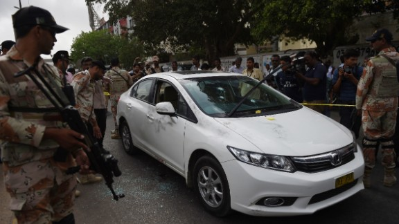Pakistani security officials inspect the bullet-riddled car of Sufi musician Amjad Sabri.