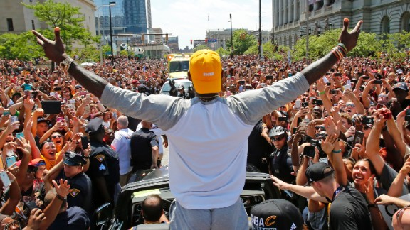 Cleveland Cavaliers star LeBron James stands in the back of a Rolls Royce as it makes its way through a victory parade in downtown Cleveland on Wednesday, June 22. The Cavaliers won their first NBA title on Sunday.