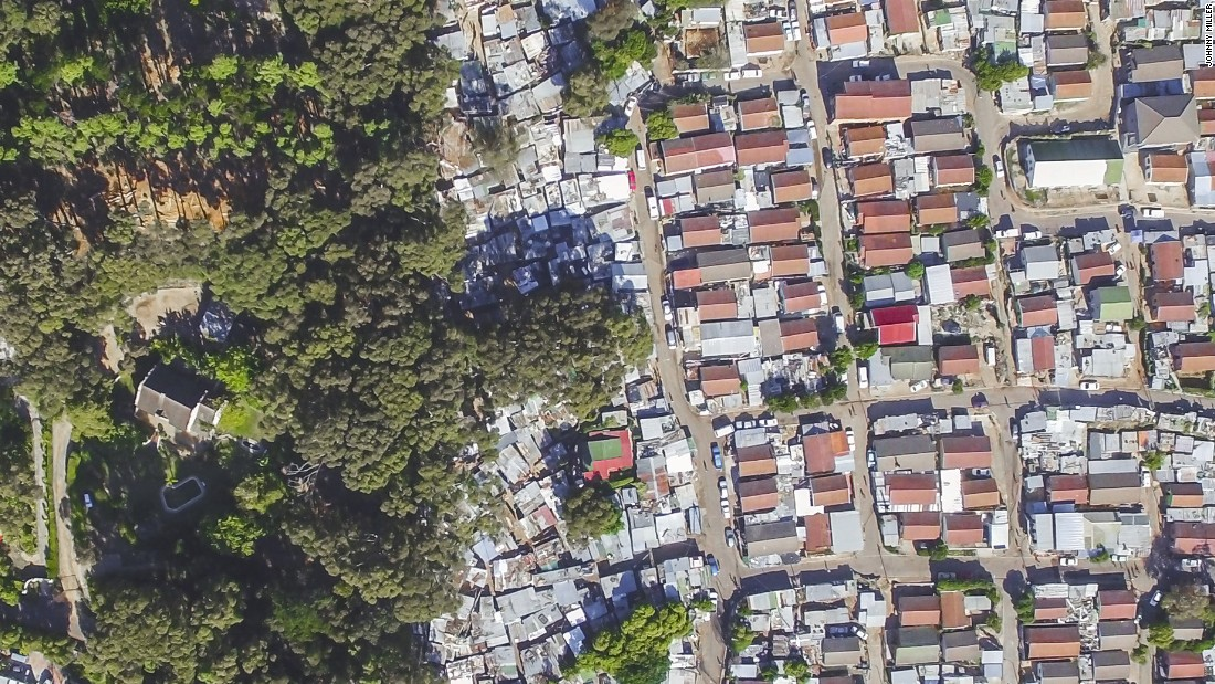 "Hout Bay is the image that seems to resonate with South Africans the most, says Miller. ""The red roofed houses are actually government houses. The tin shacks all around it are the informal settlements""."