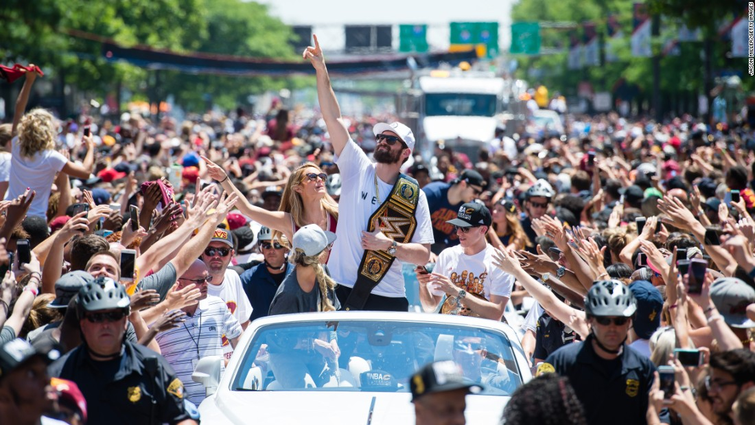Cavaliers forward Kevin Love holds a pro-wrestling title belt during the parade.