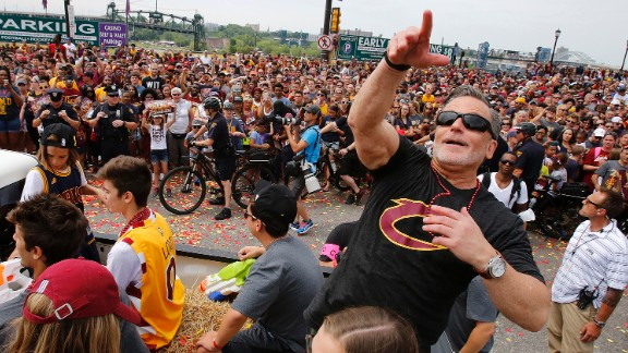 Team owner Dan Gilbert tosses beads into the crowd.