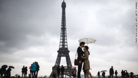 People gather on the Trocadero Square in front of the Eiffel Tower on a rainy day, on May 20, 2013, in Paris.