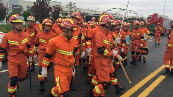 Firefighters cross a road in Funing on June 24. Provincial authorities in Jiangsu deployed a rescue team of more than 1,000 people.