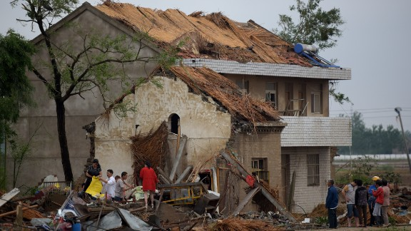 Residents survey damaged homes in Funing on June 24.