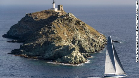 Magic Carpet, owned by Sir Lindsay Owen-Jones, rounds the Giraglia rock off Corsica's north coast.
