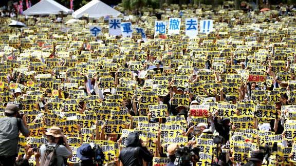 """People hold signs that say """"anger going beyond limits"""" during a demonstration in Naha, Japan, on Sunday, June 19. Tens of thousands of people have demanded an end to the United States' military presence on the Japanese island of Okinawa <a href=""""http://www.cnn.com/2016/06/20/asia/us-military-base-protests-okinawa/"""" target=""""_blank"""">following the killing of a local woman.</a> Kenneth Franklin Shinzato, a 32-year-old civilian worker who was stationed at the U.S. Kadena Air Base, was arrested on suspicion of murdering the woman."""