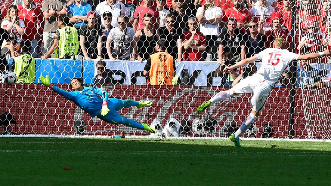 Poland defender Kamil Glik scores his penalty attempt.