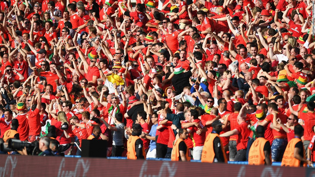 Wales supporters celebrate their team's first goal.