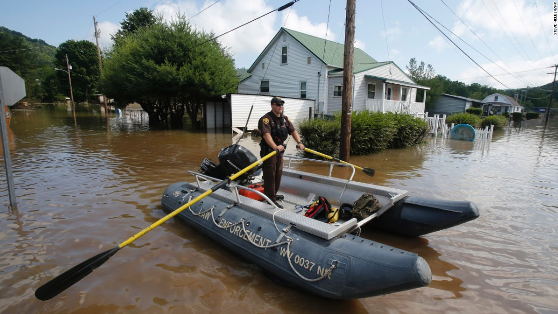 Lt. Dennis Feazell, of the West Virginia Department of Natural Resources, rows a boat as he and a co-worker search flooded homes in Rainelle on June 25.