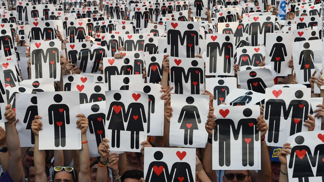 People hold placards depicting hearts and couples, during a flash mob for the annual Pride Parade in Milan, Italy, on June 25.
