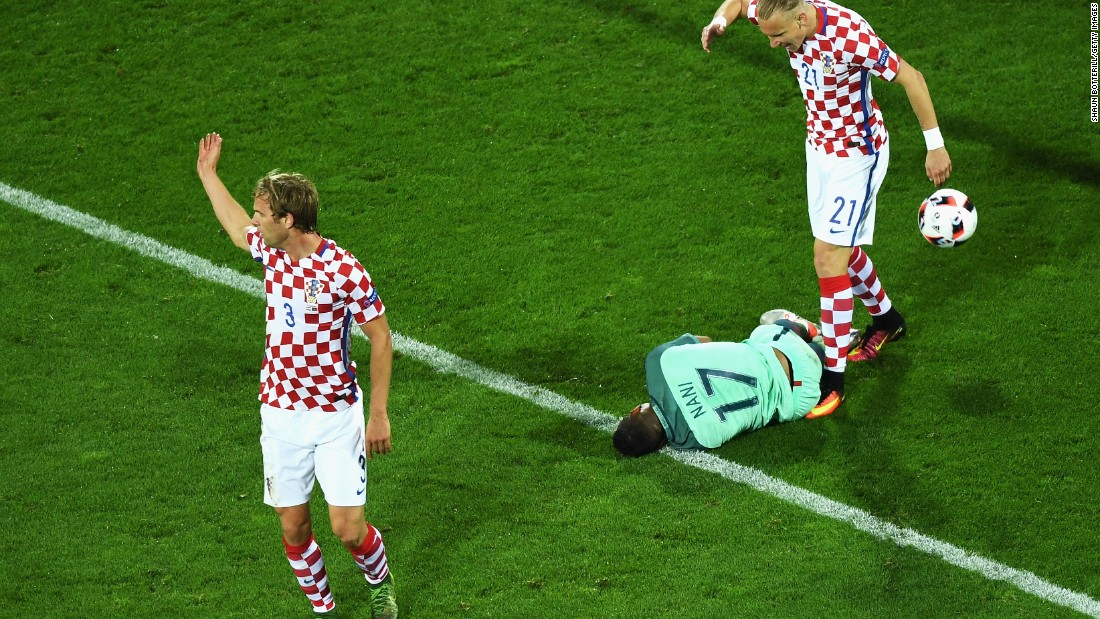 Ivan Strinic, left, and Domagoj Vida, right, of Croatia protest as Portugal forward Nani falls in the penalty area.