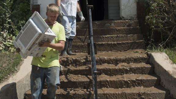 People carry personal belongings down the mud-covered steps of their home in Clendenin on June 25.