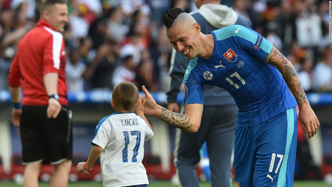 Slovakia midfielder Marek Hamsik shakes hands with his son after the game.