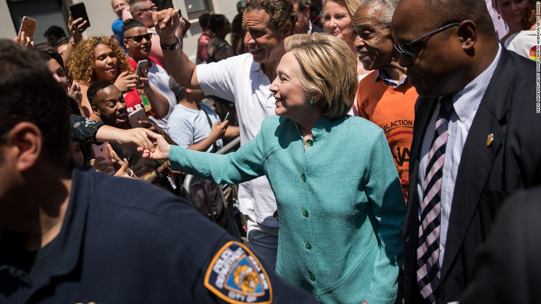 Democratic presidential candidate Hillary Clinton, flanked by New York Governor Andrew Cuomo and Rev. Al Sharpton, attends New York's parade on June 26.