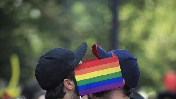Men cover their faces with rainbow flags during a gay pride parade in Bucharest, Romania, Saturday, June 25, 2016. During the years of communist rule, before 1989, homosexuality was a crime, and it is still not widely accepted among many Romanian people, with many gays avoiding to disclose their sexual orientation to avoid discrimination. (AP Photo/Vadim Ghirda)