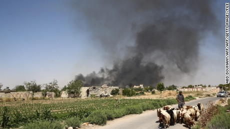 A young Syrian shepherd leads his flock on June 14, as smoke billows from a farm following a reported airstrike in Sheifuniya, near the rebel-held town of Douma, east of the capital Damascus.
