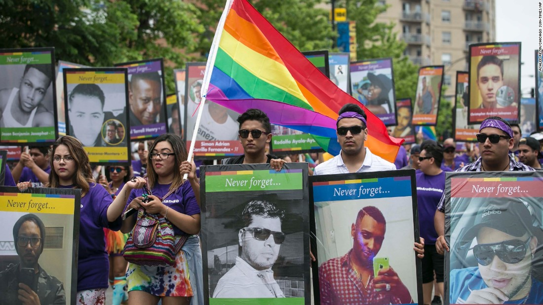 Participants in the 47th annual Chicago Pride Parade carry pictures of the Orlando shooting victims.