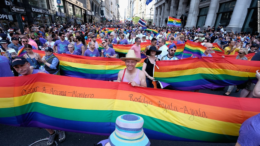 Marchers in New York carry rainbow flags.