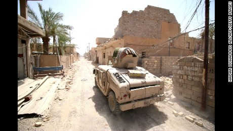 Iraqi government forces drive their armored vehicle through a street in western Falluja, Iraq, on Monday, June 27, after retaking the city from ISIS.