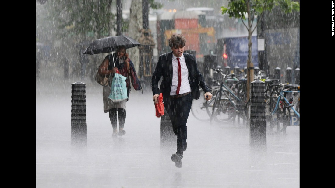 People are caught in a heavy rain shower in London on Wednesday, June 8.