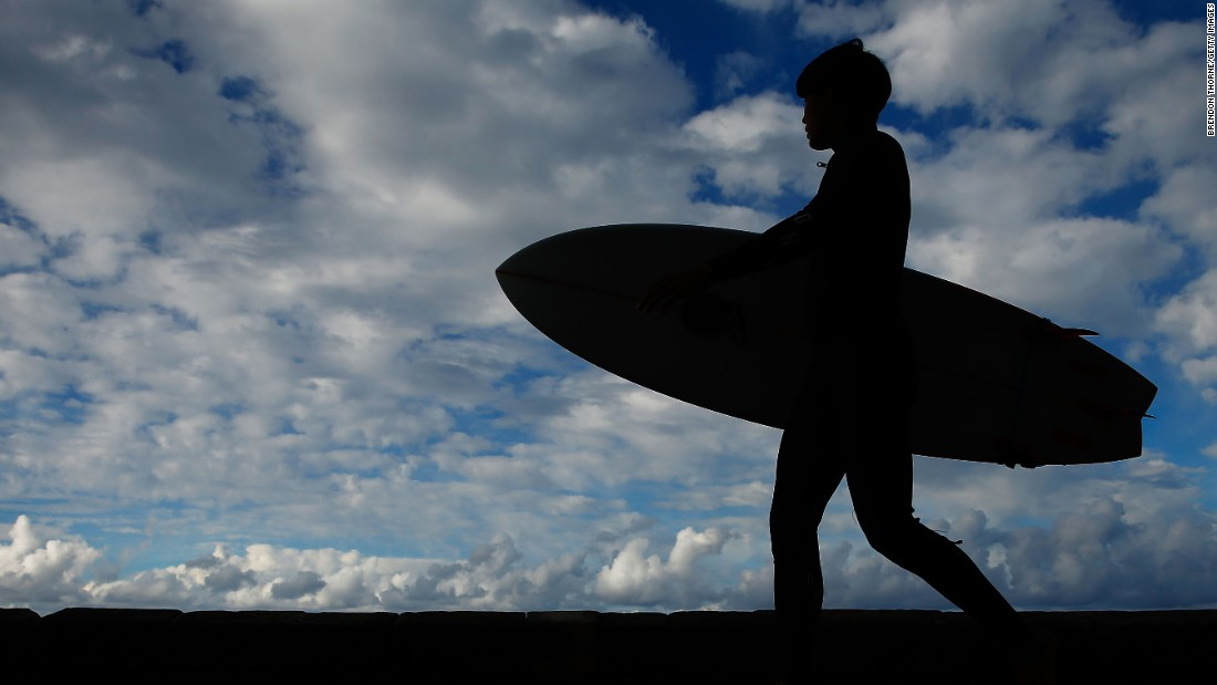 A man walks toward a Sydney beach with a surfboard on Thursday, June 2.