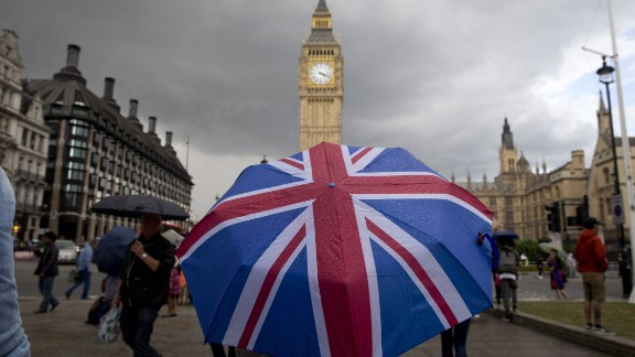 TOPSHOT - A pedestrian shelters from the rain beneath a Union flag themed umbrella as they walk near the Big Ben clock face and the Elizabeth Tower at the Houses of Parliament in central London on June 25, 2016, following the pro-Brexit result of the UK's EU referendum vote. The result of Britain's June 23 referendum vote to leave the European Union (EU) has pitted parents against children, cities against rural areas, north against south and university graduates against those with fewer qualifications. London, Scotland and Northern Ireland voted to remain in the EU but Wales and large swathes of England, particularly former industrial hubs in the north with many disaffected workers, backed a Brexit. / AFP / JUSTIN TALLIS        (Photo credit should read JUSTIN TALLIS/AFP/Getty Images)