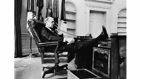 "President Gerald R. Ford talks on the telephone in the Oval Office shortly after replacing Richard Nixon. ""The empty shelves in the background are a clue to how fast the transition occurred with all of the former President's things taken out with no time to replace them with Ford mementos,"" Kennerly said."