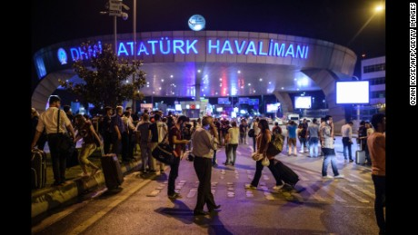 EDITORS NOTE: Graphic content / People stand outside the entrance as they leave the airport after two explosions followed by gunfire hit the Turkey's biggest airport of Ataturk in Istanbul, on June 28, 2016. 