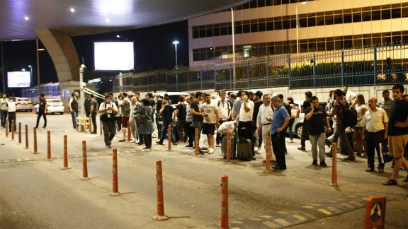 People stand outside the airport after the attack.
