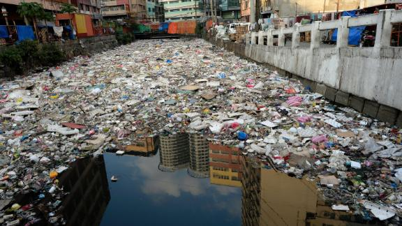 Buildings are reflected in the waters of a garbage filled river in Manila on January 23, 2016. Plastic rubbish will outweigh fish in the oceans by 2050 unless the world takes drastic action to recycle the material, a report warned January 19, on the opening day of the annual gathering of the rich and powerful in the snow-clad Swiss ski resort of Davos. AFP PHOTO / NOEL CELIS / AFP / NOEL CELIS        (Photo credit should read NOEL CELIS/AFP/Getty Images)