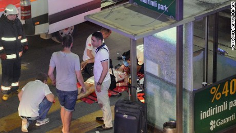 This picture obtained from the Ilhas News Agency shows emergency workers caring for an injured woman lying on the ground, after two explosions followed by gunfire hit the Turkey's biggest airport of Ataturk in Istanbul, on June 28, 2016. At least 10 people were killed on June 28, 2016 evening in a suicide attack at the international terminal of Istanbul's Ataturk airport, Turkish Justice Minister Bekir Bozdag said. Turkey has been hit by a string of deadly attacks in the past year, blamed on both Kurdish rebels and the Islamic State jihadist group.  / AFP / ILHAS NEWS AGENCY / - / Turkey OUT        (Photo credit should read -/AFP/Getty Images)
